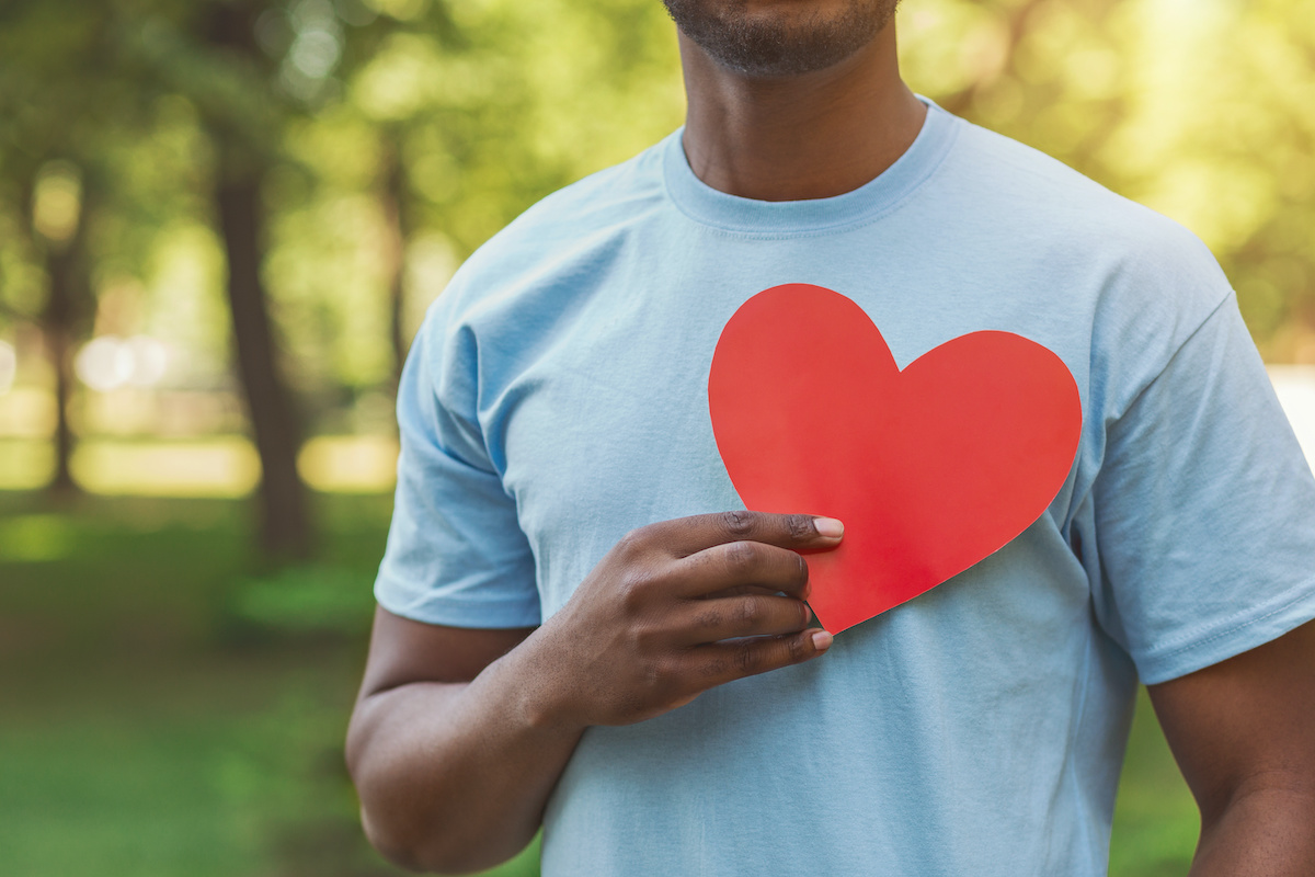 World heart day, volunteering and charity. Millennial african-american man holding red heart on his chest, free space